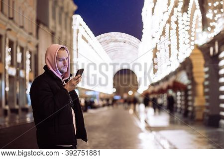 Man In Hood Looking Into His Smartphone In Background Of Night Street