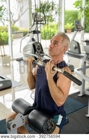 Mature Handsome Persian Man Exercising With Pull Down Machine At The Gym