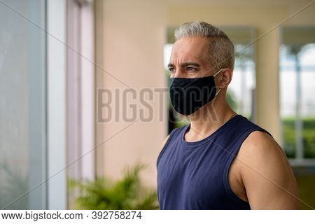 Mature Persian Man With Mask Thinking While Social Distancing At The Gym