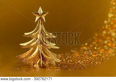 Shining Christmas Tree And Confetti In The Form Of Stars Sparkling On A Golden Background. Christmas