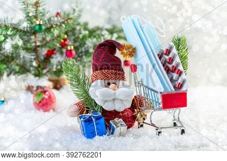 Santa With Gifts And A Metal Shopping Cart With Medical Masks, Pills And A Spruce Branch On A Snow-c
