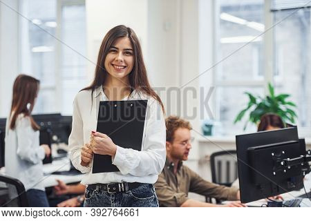 Positive Woman Standing In Front Of Young Business People That Working Together In The Modern Office