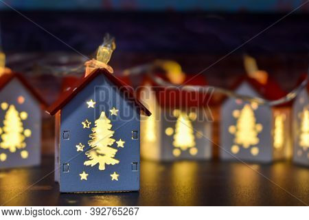 Small Christmas Houses With Christmas Tree-shaped Windows That Glow From The Inside. Christmas Garla