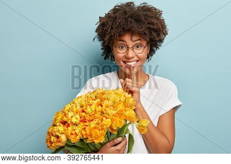 Young Pretty Lady With Curly Haircut, Makes Silence Gesture, Holds Fore Finger Over Lips, Wears Whit