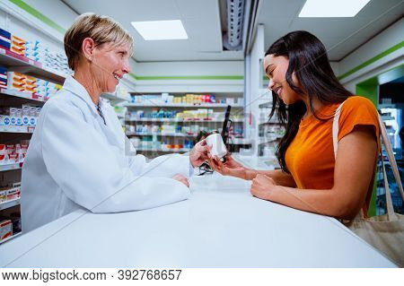 Senior Pharmacist Selling Medication To Beautiful Young Mixed Race Female Over The Counter In Chemis