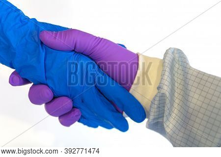Handshake In A Blue And Purple Gloves Isolated On White Background