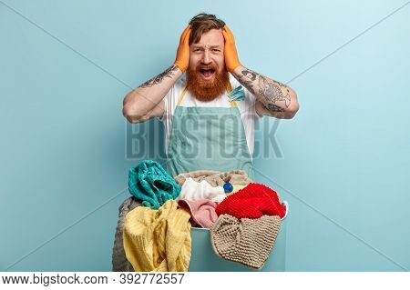 Horrified Ginger Young Man Keeps Hands On Head, Opens Mouth Widely, Wears Casual Blue Basin, Oversta