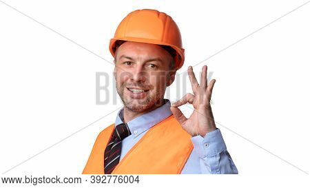 Cheerful Builder In Uniform Gesturing Ok Sign Smiling To Camera Standing On White Studio Background.