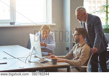 Three Male Coworkers Looking At Pc Screen And Discussing Project, Business People Working Together I