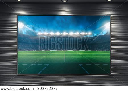 Watching A Soccer Event On A Large Tv Wall Mounted And Illuminated By Spotlights