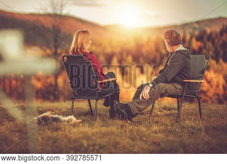 Caucasian Couple In Their 40s Seating In Front Of Scenic Vista Enjoying Their Life And The Nature. A