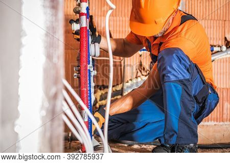 Caucasian Plumber Wearing Orange Hard Hat Installing Bathroom Water Supply Inside Newly Developed Co
