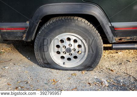 A Suv Carwith A Flat Tire Is Seen Parked On A Dirt Road.