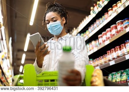 Black Lady In Mask Using Phone Shopping Buying Food Groceries Standing Wih Trolley Cart In Supermark