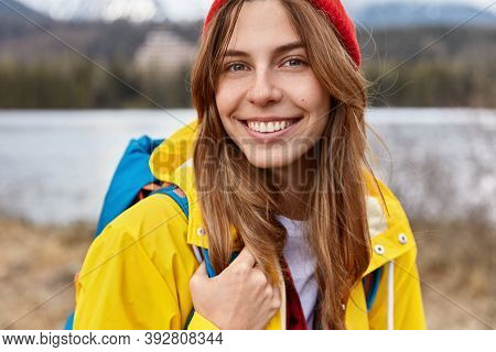 Cropped Image Of Lovely Cheerful European Woman Has Broad Tender Smile, Long Straight Hair, Wears Re