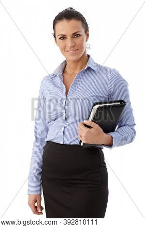 Portrait of happy casual brunette caucasian businesswoman standing in front of white background. Smiling, personal organizer in hand, looking at camera.