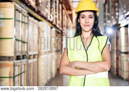 Portrait white caucasian warehouse female worker woman stand and cross arm with confidence smile in large warehouse distribution center. Business warehouse and logistic concept.