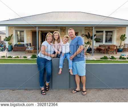Portrait Of Happy Family Of Four Embracing And Smiling In Front Of New Dream Home.