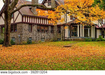 A Large Cobble And Wood Home With A Front Lawn Covered In Bright Yellow Autumn Leaves