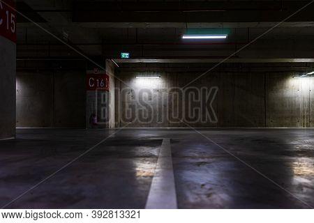 Empty Parking Lot With Overhead Dim Light, Underground Parking Garage.