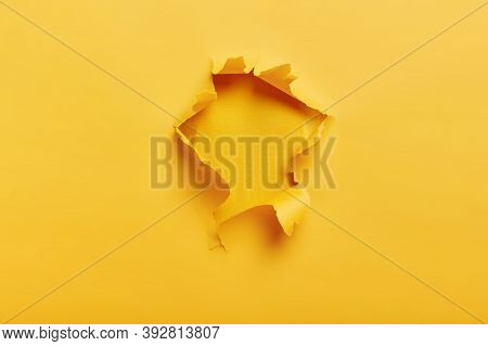Small Paper Hole With Torn Sides Over Yellow Background For Your Text, Print Or Promotional Content.