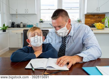 Stressed Man Working From Home And Helping Bored Son With Remote Learning During Lockdown