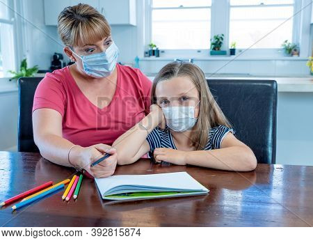 Coronavirus School Closures And Lockdown. Mum And Bored Daughter With Masks Studying Online At Home