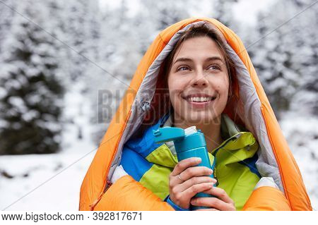 Beautiful Glad Woman Wrapped In Sleeping Bag, Drinks Hot Beverage From Thermos, Rests After Hiking O