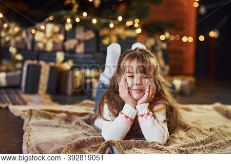 Little Girl Lying Down On The Ground In The Christmas Decorated Room.