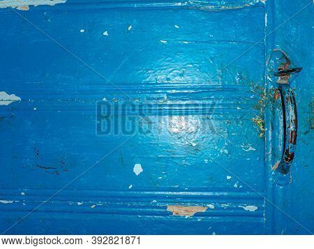 An Old Shabby Blue Wooden Door With An Iron Handle. Metal Door Handle. Shabby Old Painted Wooden Doo