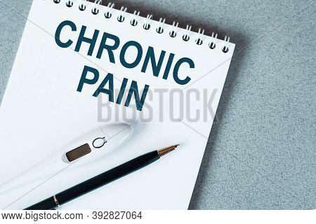 The Text Is A Chronic Pain. Top View Written On White Paper Pad On The Desktop. Medical Concept.