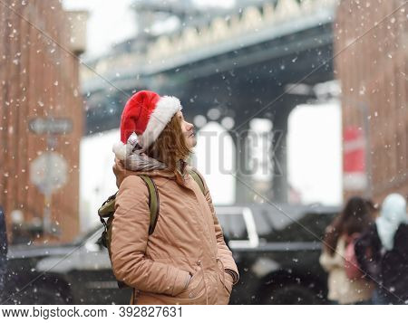 A Young Woman Tourist In A Santa Claus Hat Walks During A Snowfall In New York On Christmas Eve. Man