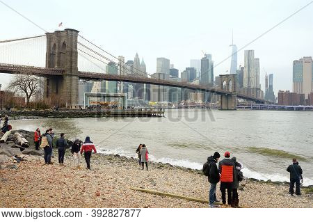 New York, Usa - December 26, 2019: Tourists Walking On Riverside Of East River And Admiring Of Famou