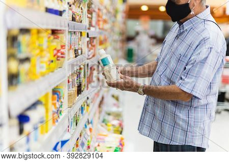Senior Man Wearing A Protective Mask In Food Shopping Store During Covid-19.