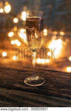 A Glass Of Champagne On A Wooden Background.bubbly. A Goblet Of Sparkling Wine. A Wineglass Of Fizz