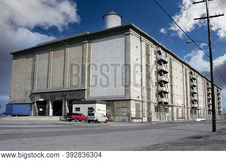 Old seaside concrete warehouse building near port and harbor facilities.
