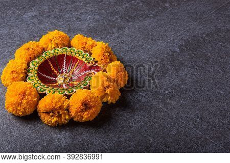 Top View Overhead Clay Lit Diya Or Oil Lamp And Yellow Flower, Studio Shot On Concrete Background, D