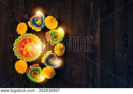 Top View Overhead Clay Lit Light A Fire Already On Diya Or Oil Lamp, Studio Shot On Black Wooden Bac