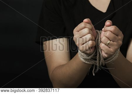 Slave Asian Woman Fears She Was Hands Tied Up With Rope Black Background. Stop Violence Against Kidn