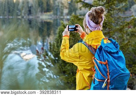 Back View Of Woman Traveler Takes Photo On Camera Of Modern Cell Phone, Captures Scenic View Near Mo