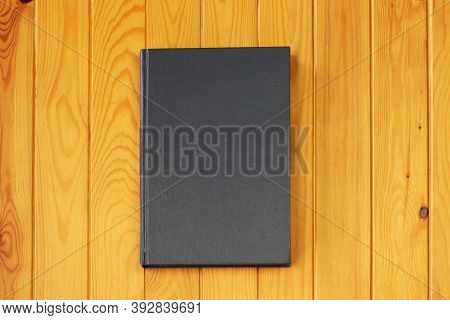 Hardcover Textbook On Wooden Table For Background And Template