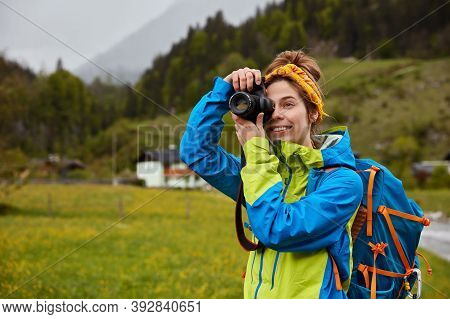 Smiling Woman Wanders In Beautiful Mountain Countryside, Keeps Camera Near Eye, Makes Photo Dressed