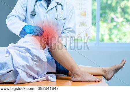 Close-up Hand Wear Medical Gloves Doctor Examining Head Of Patient With Knee Problems In Clinic, Con