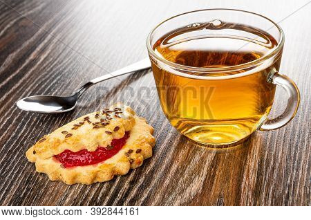 Teaspoon, Shortbread Cookie With Raspberry Jam And Linseeds, Transparent Cup With Tea On Dark Wooden