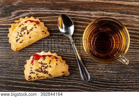 Shortbread Cookies With Raspberry Jam And Linseeds, Teaspoon, Transparent Cup With Tea On Dark Woode