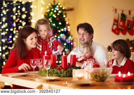 Family With Children Eating Christmas Dinner At Fireplace And Decorated Xmas Tree. Parents, Grandpar