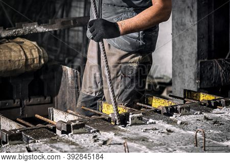 The Production Process Is The Creation Of Reinforced Concrete Pillars. Male Worker Removes Excess Ox