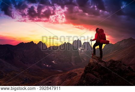 Woman Standing On Rocks Looking At Scenic Mountain Peaks And Valley, Fall In Canadian Nature. Dramat