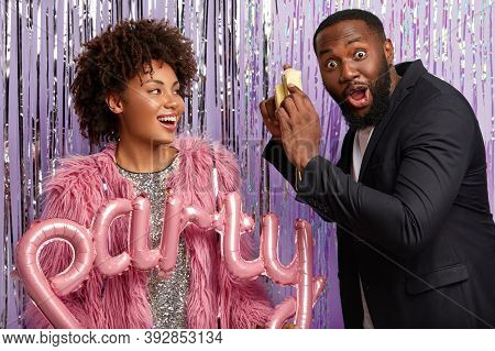 Surprised Black Man Has Thick Beard, Looks With Bugged Eyes, Holds Little Camera, Photographs Girlfr