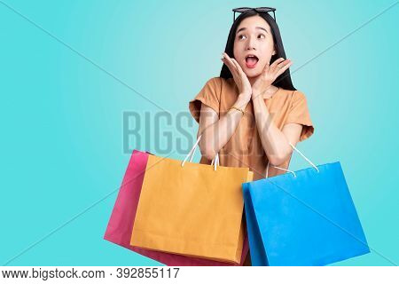 Portrait Asian Woman Carrying Colorful Shopping Bags On Isolated Blue Background , Summer Sale Conce